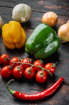 Sammlung von gemüse paprika und zwiebeln, auf altem dunklem holztischhintergrund