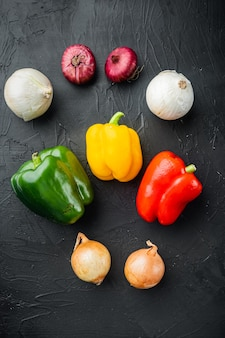 Sammlung von gemüse paprika und zwiebeln, auf schwarzem hintergrund, draufsicht flach legen