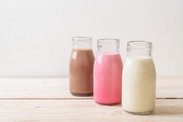 Sammlung von getränkeschokoladenmilch, rosa milch und frischer milch in der flasche auf holztisch