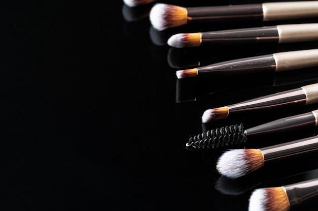 Sammlung von make-up-pinseln auf schwarzem tisch, nahaufnahme