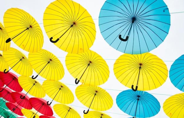 Sammlung von mehrfarbigen regenschirmen, die in offener position über einer straße hängen und schatten und schutz vor den elementen bieten.