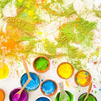 Sammlung von schüsseln mit hellen trockenen farben in der nähe von farbstapeln