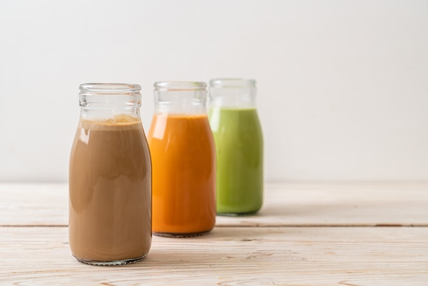 Sammlung von thailändischem milchtee des getränks, latte des matcha-grüntees und kaffee in der flasche auf holzhintergrund