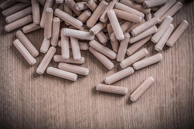 Sammlung von zylinderholz-passstiften auf holzbrett-konstruktionskonzept.