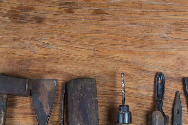 Sammlung weinleseholzbearbeitungswerkzeuge auf einer rauen werkbank und einem leeren kopienraum: zimmerei, handwerkskunst und handarbeitskonzept,