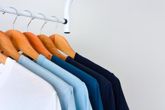Sammlungsschatten von blautonfarbt-shirts, die am hölzernen kleiderbügel auf kleiderständer hängen