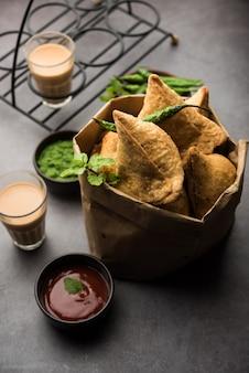 Samosa - gebratenes / gebackenes gebäck in dreiecksform mit pikanter füllung, beliebte indische tea time snacks, serviert mit grünem chutney, tomatenketchup