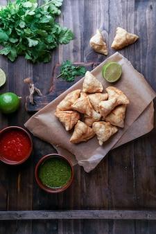 Samosa - gebratenes / gebackenes gebäck mit füllung, beliebte indische snacks, serviert in einer schüssel mit gewürzen und frischem koriander auf rustikalem hintergrund