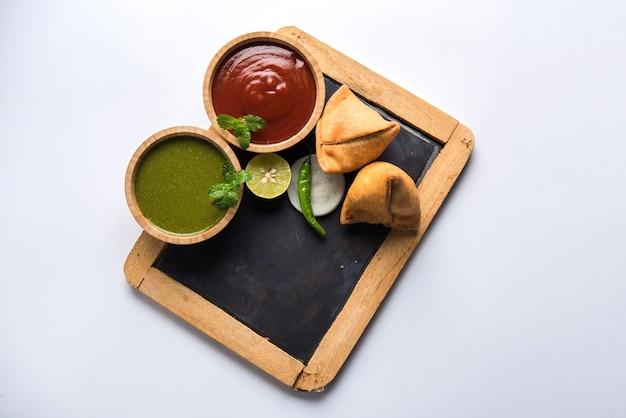 Samosa-snack serviert mit tafel oder schiefertafel für text, serviert mit ketchup und minz-chutney