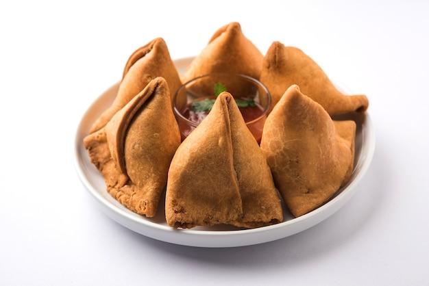 Samosa-snack serviert mit tomatenketchup und minz-chutney
