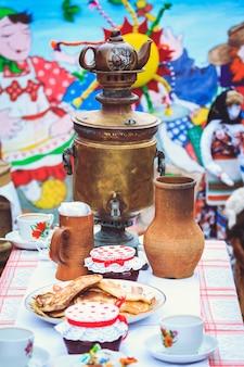 Samowar auf dem tisch neben rustikalen gerichten