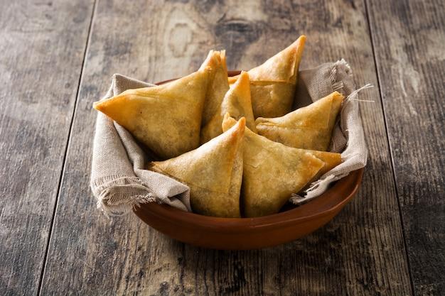 Samsa oder samosas mit fleisch und gemüse in der schüssel auf holztisch.