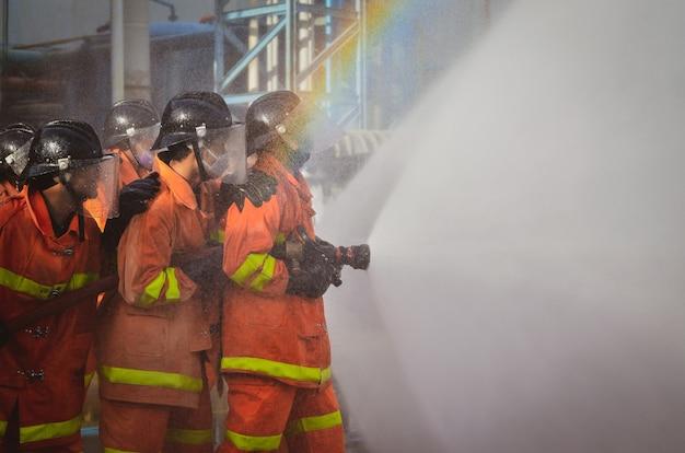 Samut sakhon, thailand - oktober 2020: feuerwehrleute sprühen am 1. oktober 2020 in samut sakhon, thailand, wasser für feuerübungen mit fabrikhintergrund.