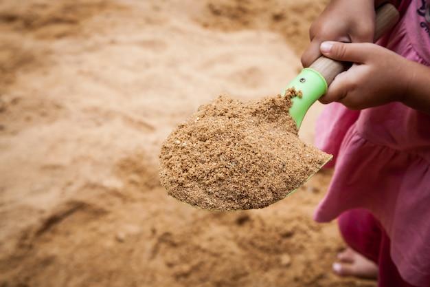 Sand auf spielzeug, kleines mädchen, das sandschaufel im spielplatz hält
