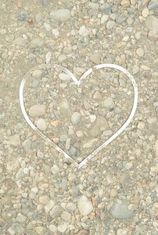 Sand mit steinen, in denen ein weißer herzförmiger rahmen platziert ist. sommerkonzept von strand und liebe