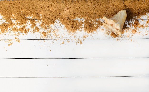 Sand und muschel auf einer weißen holzoberfläche. das konzept der entspannung auf see. die sommerstrandsaison ist geöffnet! draufsicht.