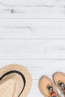 Sandalen und hut auf dem weißen hölzernen hintergrund, vertikal. sommer, urlaub, reisekonzept