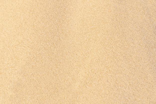Sandbeschaffenheitshintergrund auf dem strand. hellbeige meersand-texturmuster, sandstrandhintergrund.
