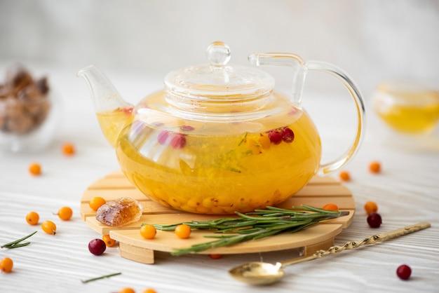 Sanddorn-tee mit preiselbeeren und rosmarin in einer glasteekanne