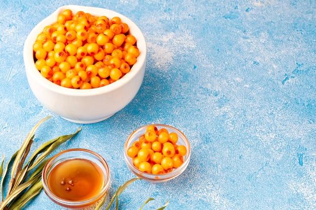 Sanddornbeeren in der schüssel und im natürlichen honig oder im sanddornöl auf blauem hintergrund