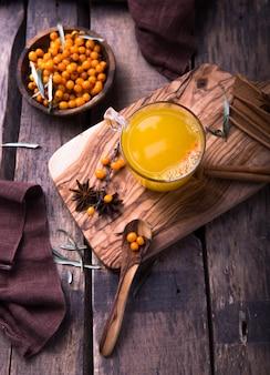 Sanddorntee mit orange in den schalen eines glases auf holztisch. kräutervitamin-tee.