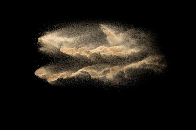 Sandexplosion lokalisiert auf schwarzem. frieren sie bewegung des sandigen staubspritzens ein.