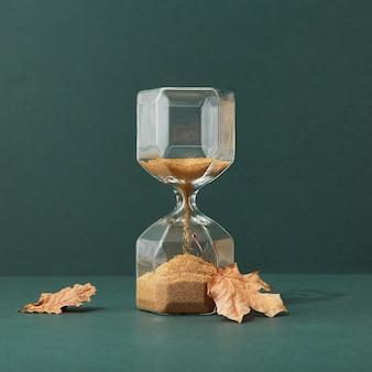 Sandglas auf stilvollem smaragdhintergrund, sanduhr mit goldsand