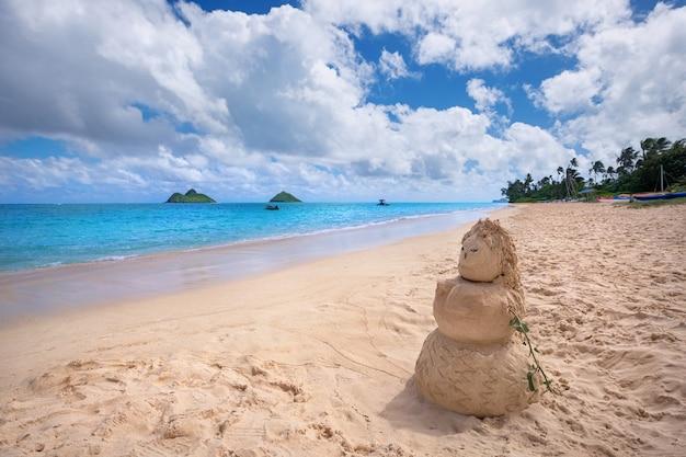 Sandige frau am lanikai-strand mit mokulua-inseln im hintergrund, kailua, o'ahu, hawaii