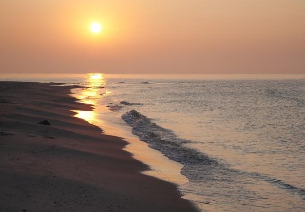 Sandiges ufer des nebligen tagesanbruchmeeres mit entferntem schatten des sonnenlichtweges und des fischerboots