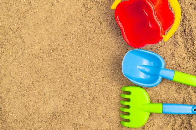 Sandkasten im freien. sandspielzeug für kinder: schaufel, rechen und eimer.