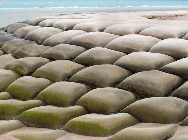 Sandsäcke oder sandbagger installiert zum schutz vor dem einsturz des strandes