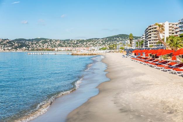 Sandstrand am türkisfarbenen meer mit liegen und hotels im südlichen ferienort.