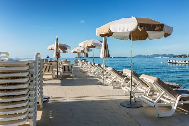 Sandstrand mit leeren sonnenliegen am pier an einem sonnigen tag im resort. französische riviera. tourismus und reisen.