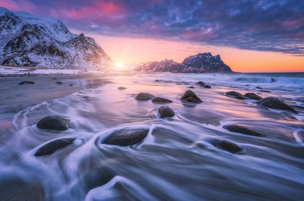 Sandstrand mit steinen im verschwommenen wasser, buntes rosa mit blauem wolkenhimmel und schneebedeckten bergen bei sonnenuntergang. utakleiv strand, lofoten inseln, norwegen.