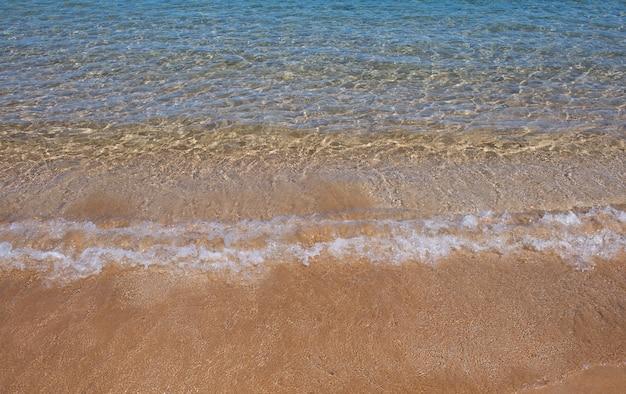 Sandstrand und tropisches meer bunte ozeanstrandlandschaft mit klarem türkisfarbenem wasser und goldenem sand...