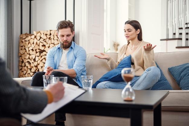 Sanduhr am psychologenkabinett mit unglücklichem verärgertem kaukasischem paar, das psychologentherapiesitzung auf hintergrund hat.