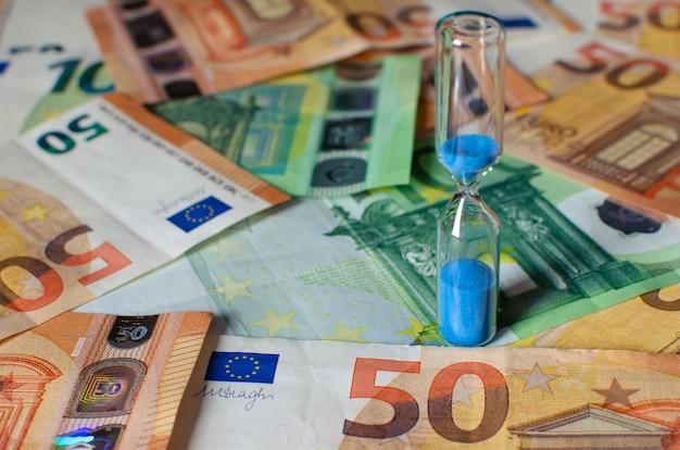 Sanduhr auf dem hintergrund von euro-banknoten. konzepte von investitionen, rentabilität, ruhestandsgeldern und geldbewegungen im laufe der zeit