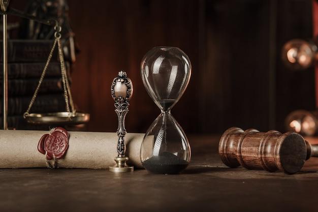 Sanduhr, bücher und stempel auf testament und letzter wille in einem gerichtssaal