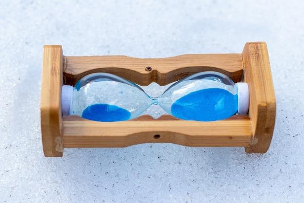 Sanduhr liegt im schnee. zeitstopp-konzept