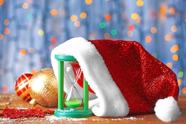 Sanduhr mit weihnachtsmütze und dekorationen gegen defokussierte lichter. weihnachts-countdown-konzept