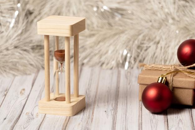 Sanduhr und pappschachtel auf einem holztisch verziert mit einer girlande und roten weihnachtsbällen für das neue jahr oder das weihnachten. post-, kurier- oder zustelldienstkonzept. kopieren sie platz