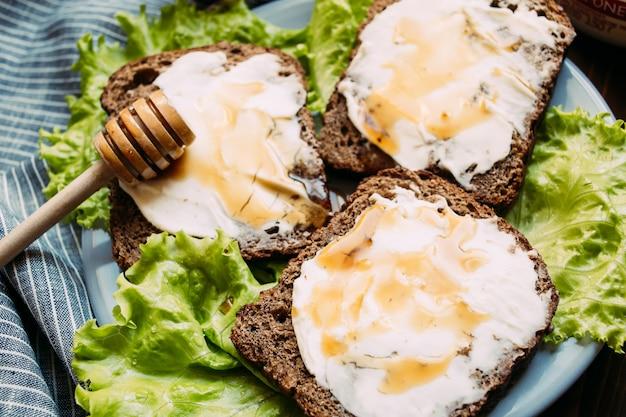 Sandwich aus roggenbrot, frischkäse, frischem salat