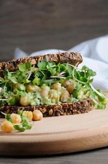 Sandwich aus roggenbrot mit müsli mit zerstoßenen avocado-kichererbsen und rettichsprossen