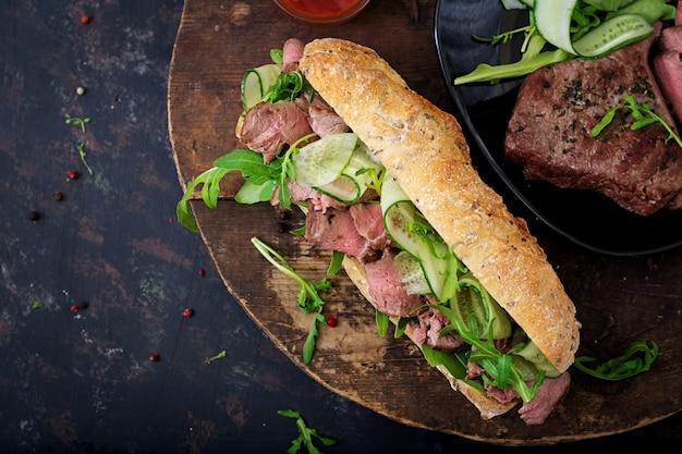 Sandwich aus vollkornbrot mit roastbeef, gurke und rucola.