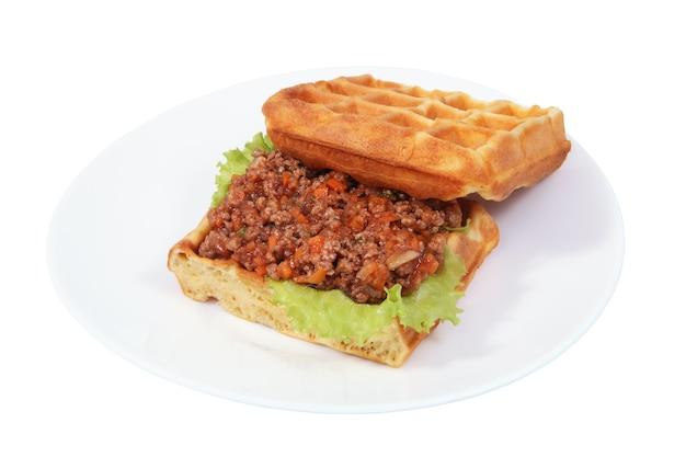 Sandwich belgische waffeln mit risotto liegt auf platte, isoliertes bild auf weißem hintergrund.
