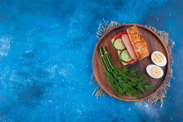 Sandwich, dill und geschnittenes ei auf einem brett, auf dem blauen hintergrund.