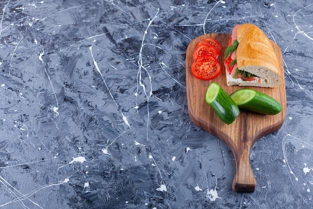 Sandwich, gurkenscheiben und tomaten auf schneidebrett auf blau.