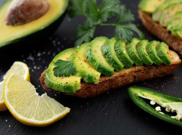 Sandwich mit avocado auf einem dunklen hausgemachten brot aus frisch geschnittenen avocados auf einem schwarzen steintisch