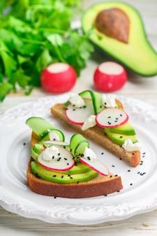 Sandwich mit avocado, rettich, gurke, petersilie, frischkäse und schwarzem sesam