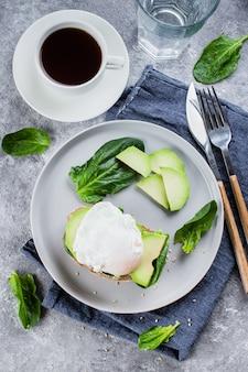 Sandwich mit avocado, spinat und poschiertem ei auf vollweizenbrot auf platte auf steinrücken
